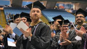 Graduate in cap and gown clapping at UNC Kenan-Flagler ceremony