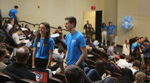 Undergraduate students stand in Koury auditorium at UNC Kenan-Flagler during Fall 2019 orientation
