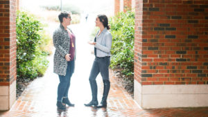 Meredith Tozzer and Becca Jordan talking in front of McColl building