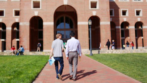 Two male business students walk towards front arches of Kenan-Flagler McColl building