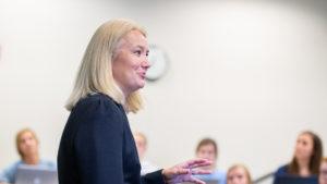 Standing in classroom professor Claudia Kubowicz Malhotra is teaching undergraduate students