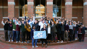 Family Enterprise Center students cheering holding flag at UNC Kenan-Flagler 2019