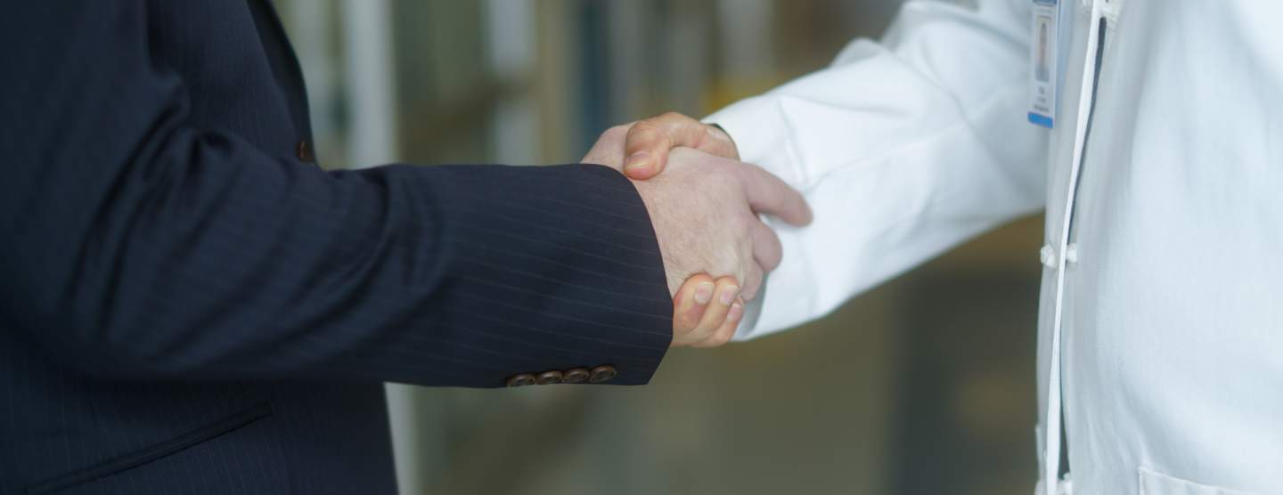 One man in a doctor's lab coat shaking hands with a man in a suit