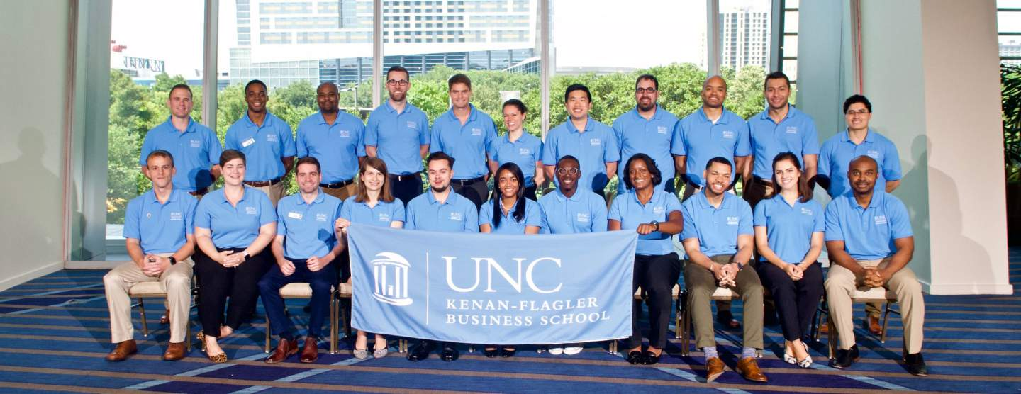 The Consortium graduating class of 2021. 22 students sit wearing matching Carolina Blue shirts holding a UNC Kenan-Flagler Business School flag.